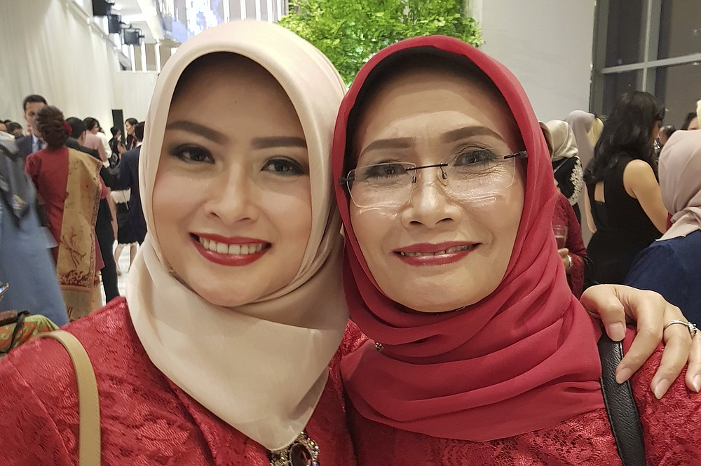 In this photo released by Eva Rahmi family, Rahmi and her mother Ismy Latifah, right, pose for a photo in Jakarta, Indonesia, Jan 28, 2018. Jan 28, 2018. Salama worries that authorities in Jakarta, Indonesia's sprawling capital, are acting too soon to lift restrictions put in place two months ago to fight the spread of the coronavirus. Salama has reason to be concerned. She saw firsthand the tremendous agony the virus can inflict when her mother and father both died from COVID-19 within two days of each other. (Eva Rahmi family via AP)