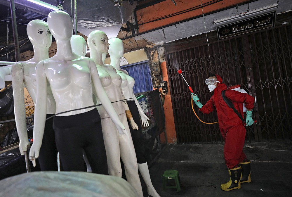 FILE - In this June 4, 2020, file photo, a fireman sprays disinfectant at mannequins as a precaution against coronavirus outbreak, at Tanah Abang textile market in Jakarta, Indonesia. As Indonesia's overall virus caseload continues to rise, Jakarta's governor has moved to restore normalcy by lifting some restrictions, saying that the spread of the virus in the city of 11 million has slowed down after peaking in mid-April. This has raised concerns among some, with experts warning that reopening too soon can cause Jakarta to be hit with a second wave of the virus. (AP Photo/Dita Alangkara, File)