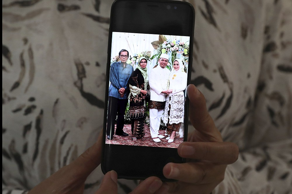Eva Rahmi shows her mobile phone that displays her parents Teten Syamsir, left, and Ismy Latifah, second from left, and her husband Andi Saloko, second from right, on their wedding day, in Jakarta, Indonesia, Tuesday, June 2, 2020. Salama worries that authorities in Jakarta, Indonesia's sprawling capital, are acting too soon to lift restrictions put in place two months ago to fight the spread of the coronavirus. This has raised concerns among some, with experts warning that reopening too soon can cause Jakarta to be hit with a second wave of the virus. (AP Phtoto/Tatan Syuflana)