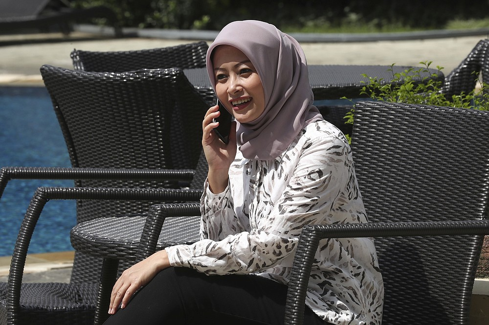 Eva Rahmi talks with her mobile phone by the swimming pool at an apartment in Jakarta, Indonesia, Tuesday, June 2, 2020. Salama, who lives in Jakarta with her husband, worries that authorities in Jakarta, Indonesia's sprawling capital, are acting too soon to lift restrictions put in place two months ago to fight the spread of the coronavirus. This has raised concerns among some, with experts warning that reopening too soon can cause Jakarta to be hit with a second wave of the virus. (AP Phtoto/Tatan Syuflana)