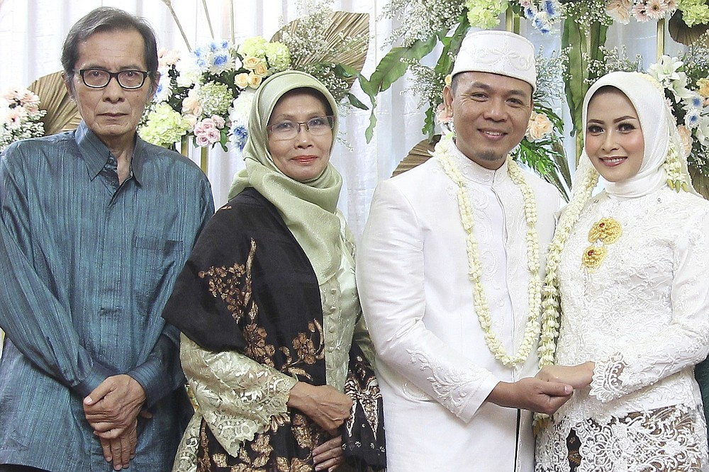In this photo released by Eva Rahmi family, Rahmi's parents Teten Syamsir, left, and Ismy Latifah, second from left, and her husband Andi Saloko, second from right, pose for a photo taken on their wedding day, March 3, 2019, in Jakarta, Indonesia. Salama worries that authorities in Jakarta, Indonesia's sprawling capital, are acting too soon to lift restrictions put in place two months ago to fight the spread of the coronavirus. Salama, who lives in Jakarta with her husband, has reason to be concerned. She saw firsthand the tremendous agony the virus can inflict when her mother and father both died from COVID-19 within two days of each other. (Eva Rahmi family via AP)