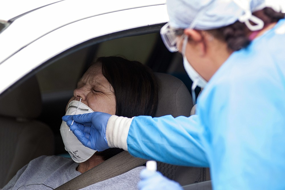 FILE - In this April 24, 2020, file photo, Regina Nelson, left, is tested for the coronavirus by Gina Johnson, a nurse tech, at the Bono Family Medical Clinic drive-thru testing site in Bono, Ark. Coronavirus cases are rising in nearly half the U.S. states, as states are rolling back lockdowns. (Quentin Winstine/The Jonesboro Sun via AP, File)