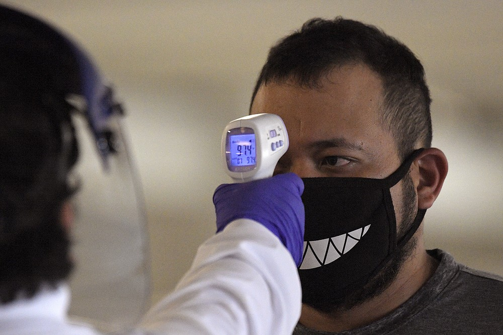 Jose Ramirez has his temperature checked before entering Universal CityWalk, Thursday, June 11, 2020, near Universal City, Calif. The tourist attraction, which had been closed due to the coronavirus outbreak recently re-opened. The Universal Studios tour is still closed. (AP Photo/Mark J. Terrill)
