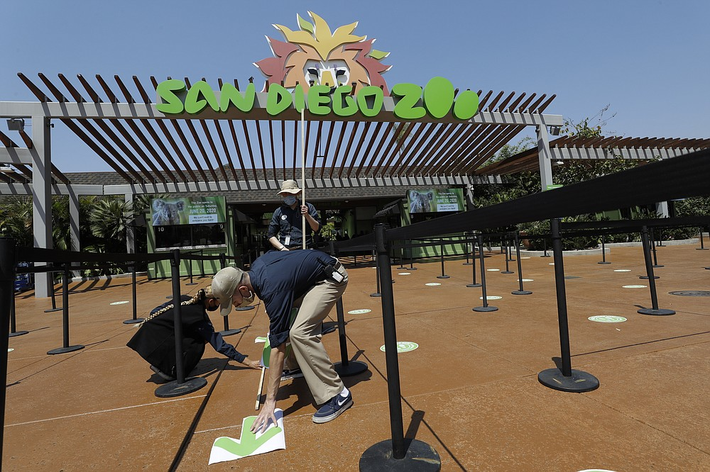 Devon Prince, front, puts down a sticker to guide visitors at the San Diego Zoo once it reopens, as Emmanuel Lopez, behind and Ariel Hayes look on, Thursday, June 11, 2020, in San Diego. California's tourism industry is gearing back up with the state giving counties the green light to allow hotels, zoos, aquariums, wine tasting rooms and museums to reopen Friday. (AP Photo/Gregory Bull)