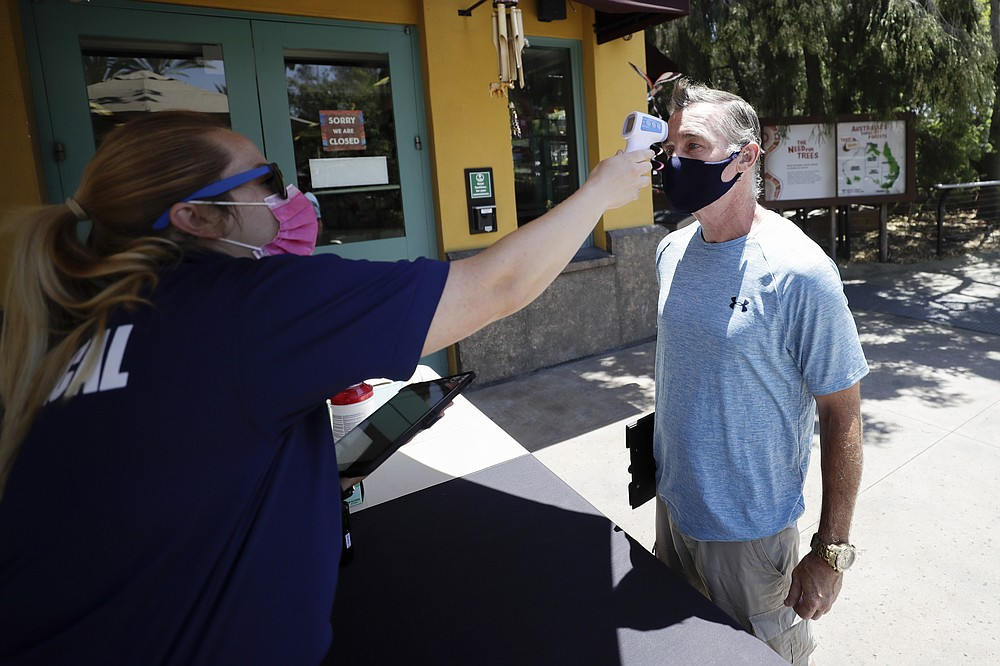 Health services worker Summer Deibert, left, checks the temperature of James McCluskey, right, as he arrives for work before the reopening of the San Diego Zoo, Thursday, June 11, 2020, in San Diego. California's tourism industry is gearing back up with the state giving counties the green light to allow hotels, zoos, aquariums, wine tasting rooms and museums to reopen Friday. (AP Photo/Gregory Bull)