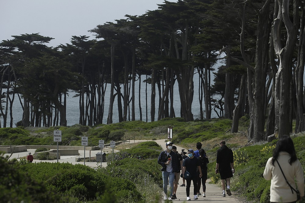 FILE - In this April 24, 2020, file photo people wear masks amid the coronavirus pandemic while walking on a path at Land's End in San Francisco. Lawmakers have reached bipartisan agreement on an election-year deal to double spending on a popular conservation program and devote nearly $2 billion a year to improve and maintain national parks. (AP Photo/Jeff Chiu, File)