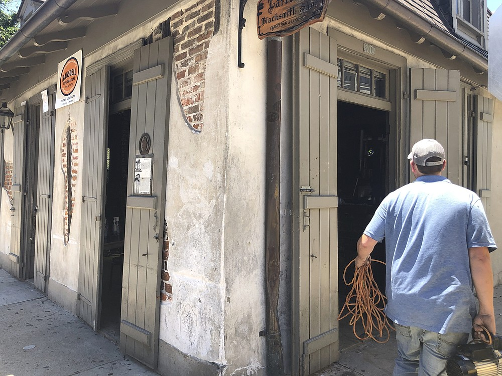 In this Friday, June 12, 2020 photo, a worker carries equipment into Lafitte's Blacksmith Shop, a bar on Bourbon Street in New Orleans.  The city is allowing bars to open – with limited capacity and without live music – on Saturday. Bars were among the businesses shut down in mid-March as coronavirus infections increased in New Orleans and Louisiana became a hot spot for the disease. (AP Photo/Kevin McGill)