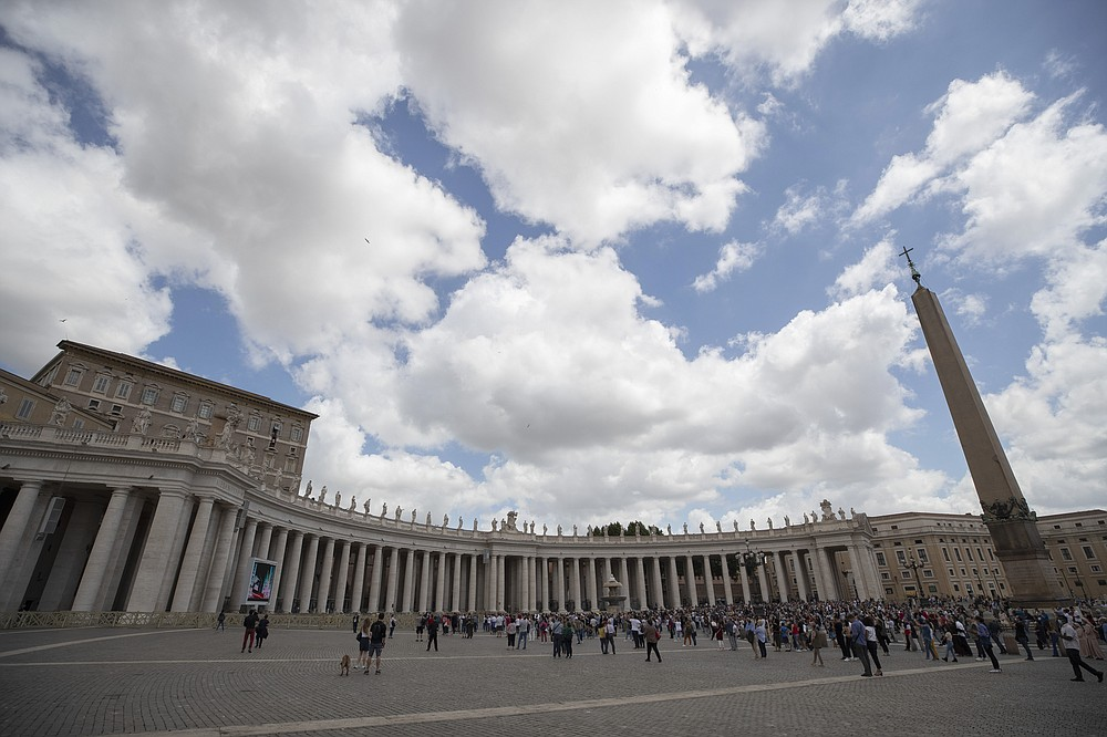 People gather in St. Peter's Square as Pope Francis delivers his Angelus prayer from the window, top, of his studio overlooking the square, Sunday, June 14, 2020. (AP Photo/Alessandra Tarantino)