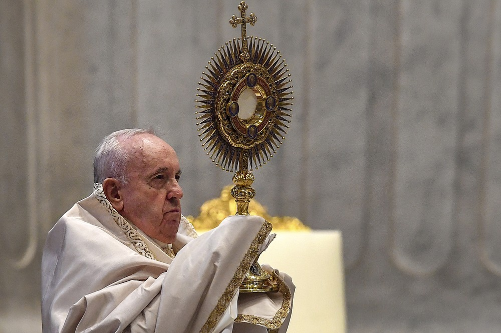 Pope Francis holds a monstrance as he celebrates a Corpus Domini Mass inside St. Peter's Basilica at the Vatican, Sunday, June 14, 2020.  (Tiziana Fabi/Pool Photo via AP)