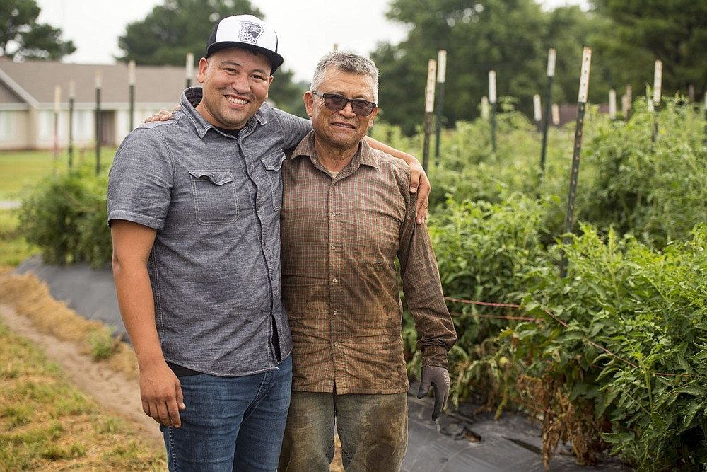 NWA Democrat Gazette/SPENCER TIREY   Rafael Rios, left, stand with his father Hector Rios at thier family Friday July28, 2017, in Rogers. Rafael Rios and his family are playing an interesting role in the Bentonville culinary scene. Refael Rios operates YeyoÕs food truck in downtown Bentonville. His family also owns a farm in Rogers, which supplies several restaurants in Bentonville. His next step is opening a physical location in the Eighth Street Market.