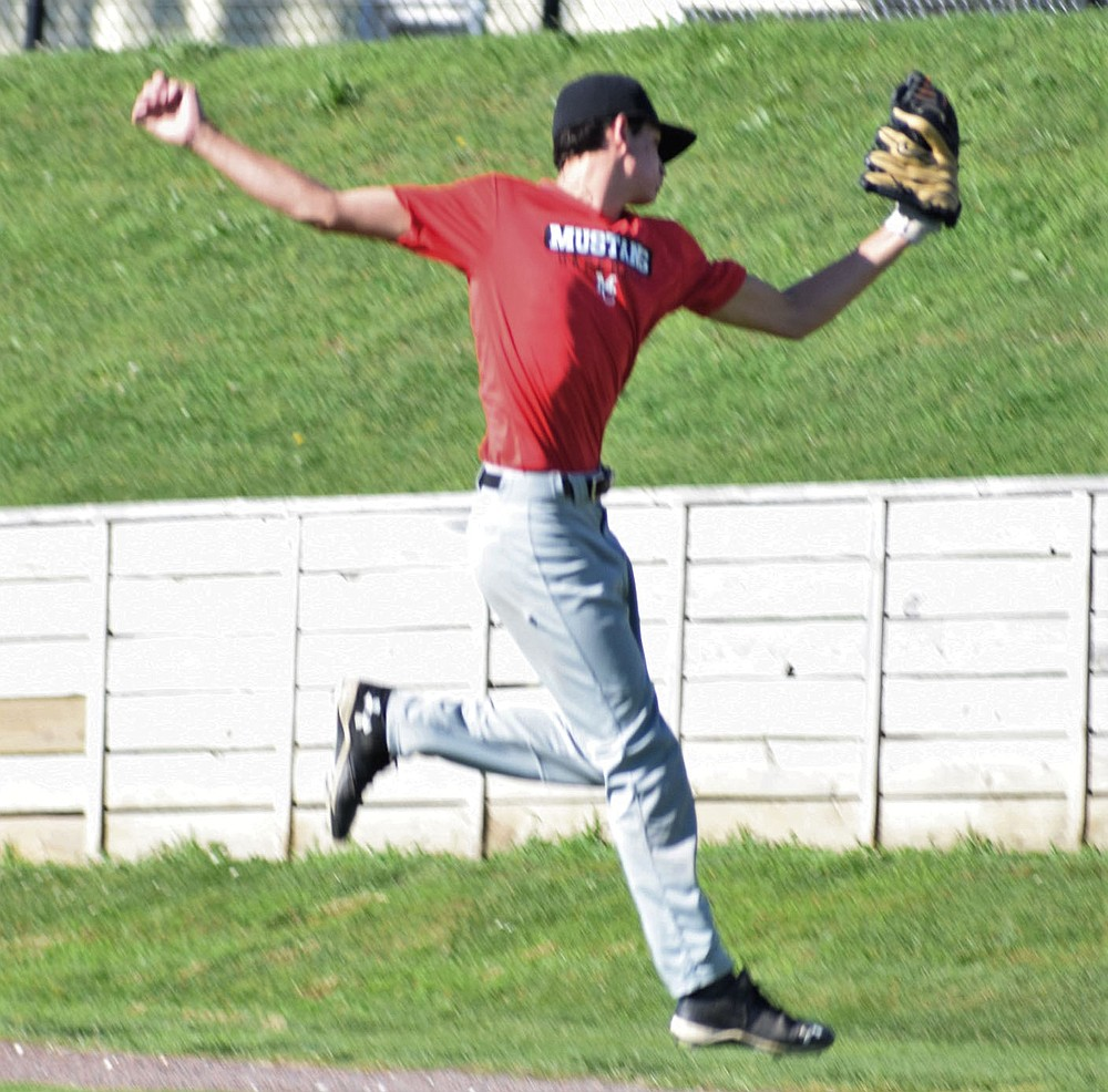 RICK PECK/SPECIAL TO MCDONALD COUNTY PRESS McDonald County center fielder Jackson Behm flies through the air to make a catch  during McDonald County's 6-3 loss on June 10 to Webb City in an 18U 8-on-8 league game at Joe Becker Stadium in Joplin.