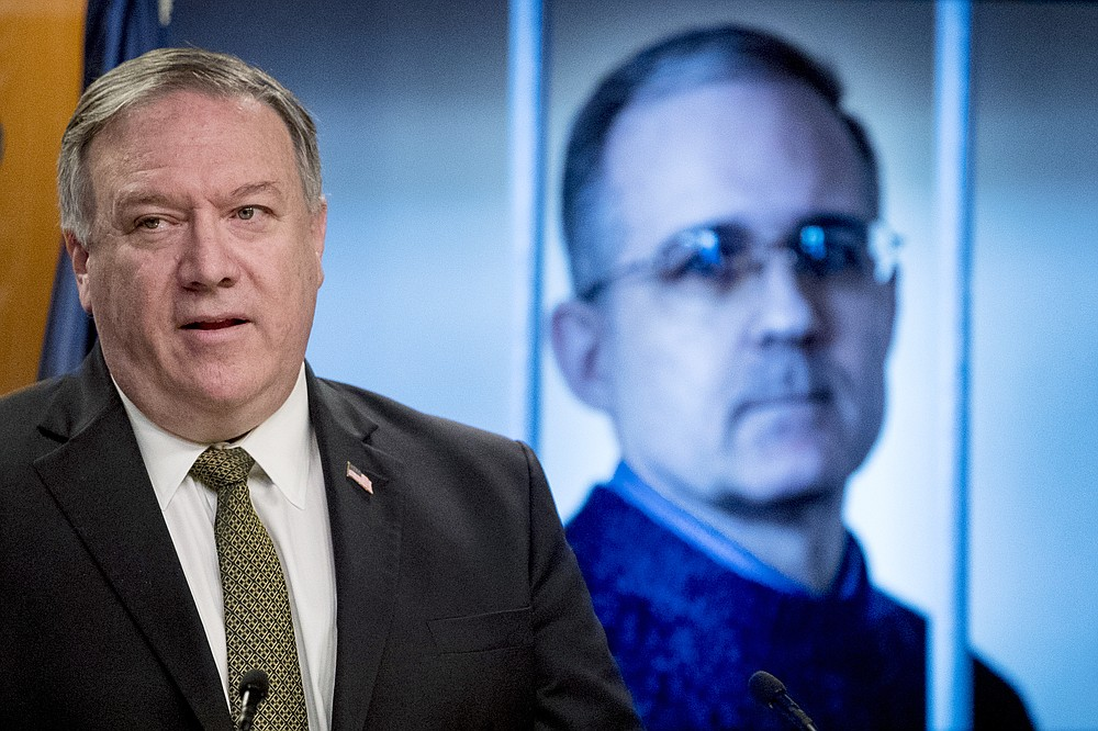 An image of Paul Whelan, a former U.S. marine who was arrested for alleged spying in Moscow, is displayed behind Secretary of State Mike Pompeo as he speaks during a news conference at the State Department in Washington, Wednesday, June 10, 2020. (AP Photo/Andrew Harnik, Pool)