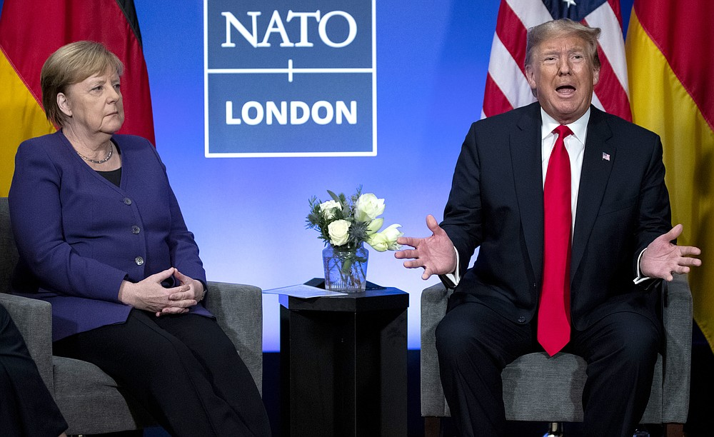 FILE - In this Wednesday, Dec. 4, 2019 file photo President Donald Trump meets with German Chancellor Angela Merkel during the NATO summit at The Grove in Watford, England. After more than a year of thinly veiled threats that the United States could start pulling troops out of Germany unless the country increases its defense spending to NATO standards, President Donald Trump appears to be going ahead with the hardball approach with a plan to reduce the American military presence in the country by more than 25 percent.  (AP Photo/ Evan Vucci, file)