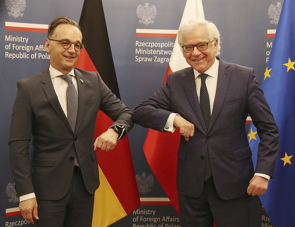 German Foreign Minister Heiko Maas,left, and Polish Foreign Minister Jacek Czaputowicz greet each other with an elbow bump, used instead of a handshake during the coronavirus pandemic, in Warsaw, Poland, Tuesday, June 16, 2020.(AP Photo/Czarek Sokolowski)