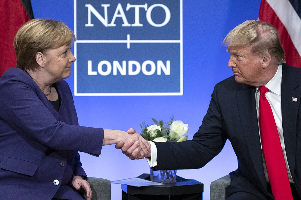 FILE - In this Wednesday, Dec. 4, 2019 file photo President Donald Trump Trump shakes hands with German Chancellor Angela Merkel during the NATO summit at The Grove in Watford, England. After more than a year of thinly veiled threats that the United States could start pulling troops out of Germany unless the country increases its defense spending to NATO standards, President Donald Trump appears to be going ahead with the hardball approach with a plan to reduce the American military presence in the country by more than 25 percent.  (AP Photo/ Evan Vucci, file)