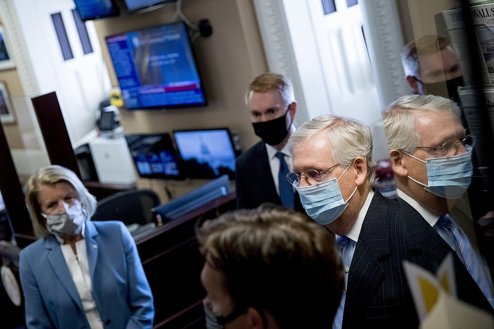 Senate Majority Leader Mitch McConnell of Ky., right, accompanied by Sen. Shelley Moore Capito, R-W.Va., left, and Sen. James Lankford, R-Okla., center, stands with other Republican senators before a news conference to announce a Republican police reform bill on Capitol Hill, Wednesday, June 17, 2020, in Washington. (AP Photo/Andrew Harnik)