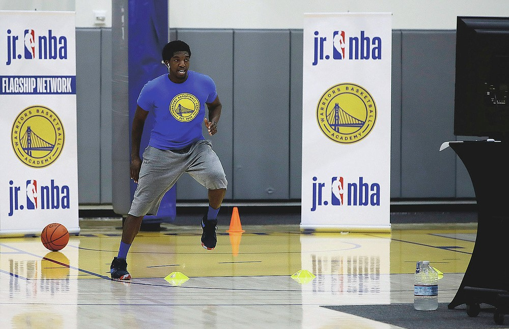 In this photo taken on Tuesday, June 9, 2020, Aalim Moor performs a drill for virtual students at Golden State Warriors basketball camp in Oakland, Calif. The State had to adapt their popular youth basketball camps and make them virtual given the COVID-19 pandemic. (AP Photo/Ben Margot)