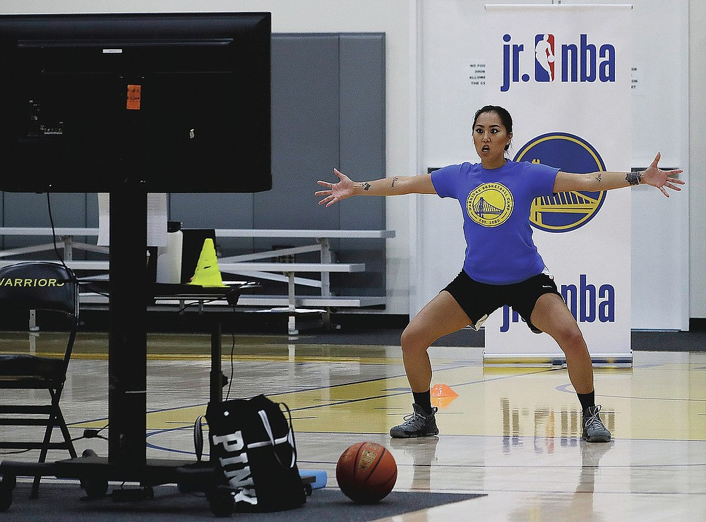 In this photo taken on Tuesday, June 9, 2020, coach Chanel Antonio leads a drill with her virtual students at Golden State Warriors basketball camp in Oakland, Calif. The Warriors had to adapt their popular youth basketball camps and make them virtual given the COVID-19 pandemic. (AP Photo/Ben Margot)