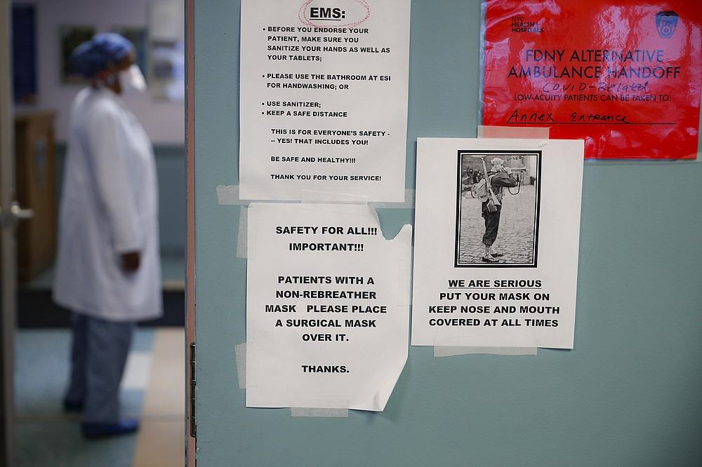 COVID-19 safety reminders hang on a wall in the emergency department intake area at NYC Health + Hospitals Metropolitan, Wednesday, May 27, 2020, in New York. At hospitals around the country, nurses, doctors and other health care workers are reckoning with the psychological toll of the virus fight, coupled with fears that the disease could flare anew later this year. (AP Photo/John Minchillo)