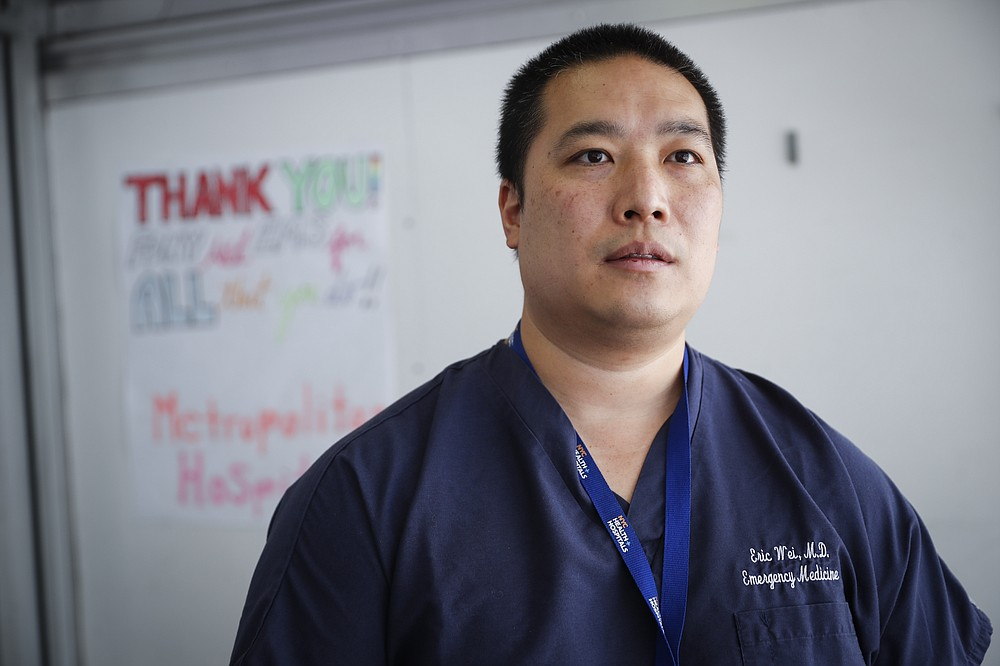 Dr. Eric Wei, vice president and chief quality officer for NYC Health + Hospitals, is interviewed outside the emergency department at NYC Health + Hospitals Metropolitan, Wednesday, May 27, 2020, in New York. At hospitals around the country, nurses, doctors and other health care workers are reckoning with the psychological toll of the virus fight, coupled with fears that the disease could flare anew later this year. (AP Photo/John Minchillo)