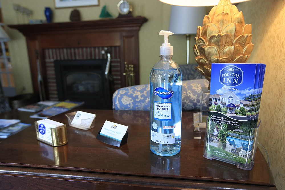 In this Wednesday, June 10, 2020, photo, hand sanitizer is provided for guests in the lobby of the Cod Cove Inn in Edgecomb, Maine. Home-bound travelers desperate to venture out for the first time since the pandemic are confronting a vacation landscape this summer that may require coronavirus tests for the family and even quarantines. (AP Photo/Robert F. Bukaty)