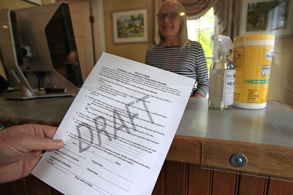 "In this Wednesday, June 10, 2020, photo, a draft of a coronavirus pandemic compliance form is held by Cod Cove Inn owner Ted Hugger in Edgecomb, Maine. The form is part of the ""Keep Maine Healthy"" plan the state is proposing, requiring out-of-state visitors to verify they are free of the virus. Residents of New Hampshire and Vermont are exempt. (AP Photo/Robert F. Bukaty)"