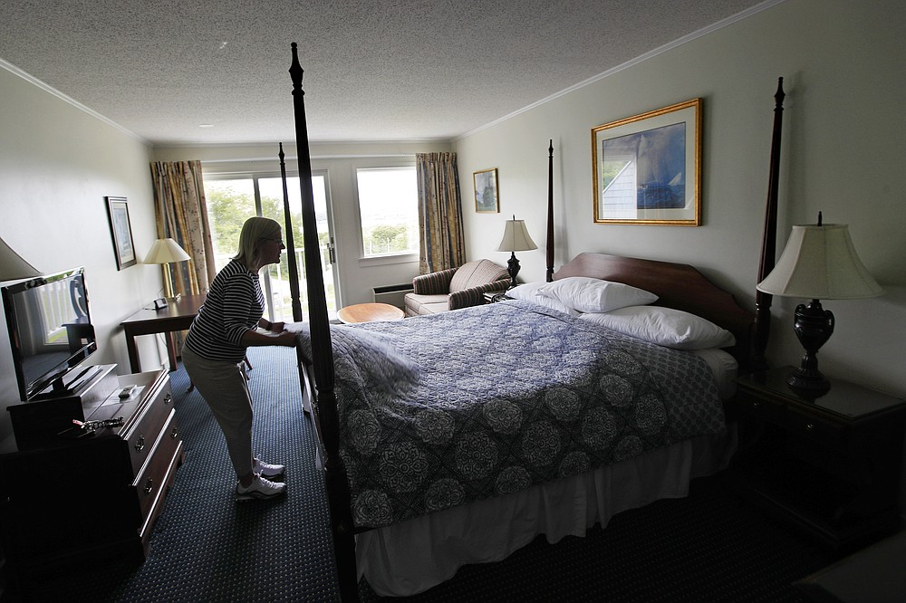 In this Wednesday, June 10, 2020, photo, Cod Cove Inn owner Jill Hugger adjusts a bedspread in a room at her inn in Edgecomb, Maine. During the coronavirus pandemic, inn owners are dealing with working to reopen while the state grapples with how to help prevent the spread of the virus. (AP Photo/Robert F. Bukaty)