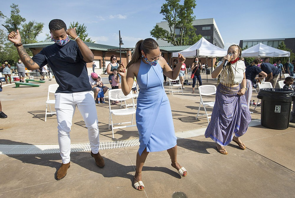 Brandon Claybrook (from left) of Rogers, wife Karrié Claybrook and Emma Willis dance Friday, June 19, 2020, during a Juneteenth cookout at Lawrence Plaza in Bentonville. Go to nwaonline.com/200620Daily/ to see more photos. (NWA Democrat-Gazette/Ben Goff)