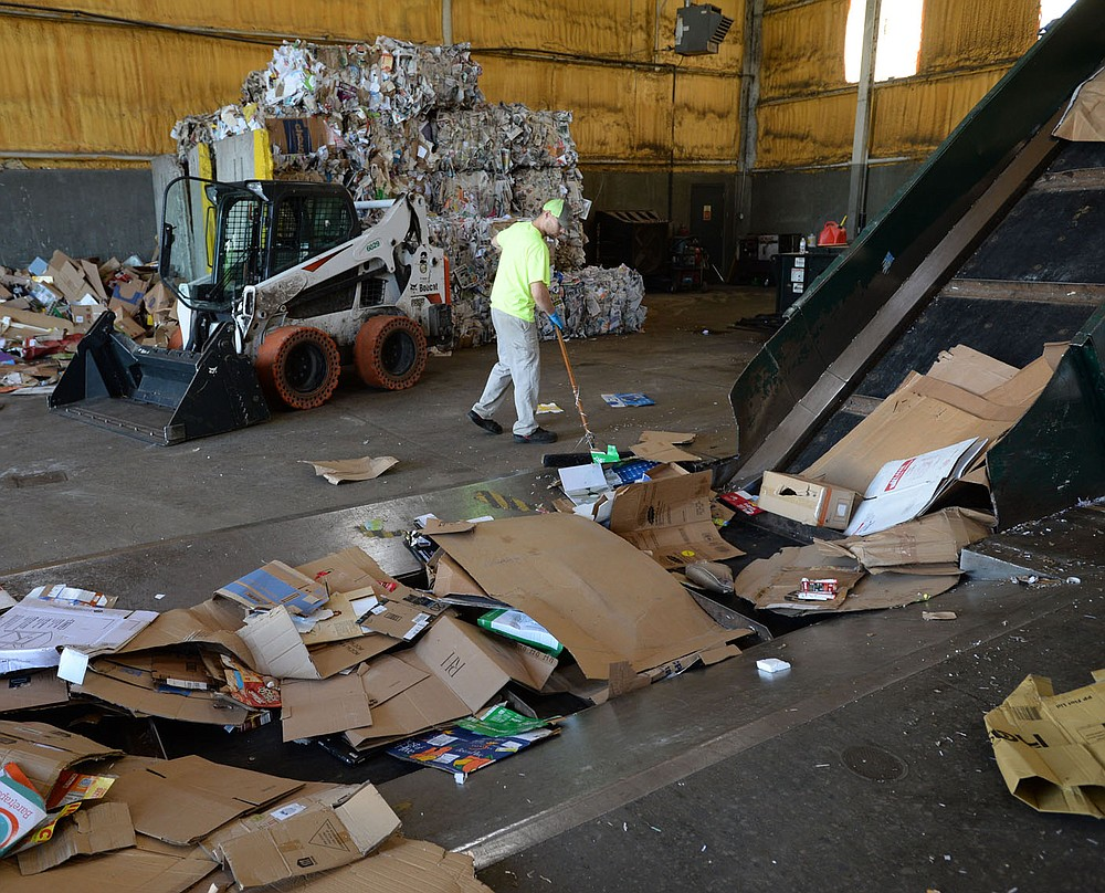 Christopher Richardson, a worker with the city of Fayetteville's Recycling and Trash Collection Division, sweeps boxes that fell from a skid steer loader Friday, June 19, 2020, while loading corrugated cardboard into a baling machine at the division's facility. Recycling collection during suspension of the curbside program was about 79% of what it was from March to June last year. The city's curbside service resumes Monday.Visit nwaonline.com/200621Daily/ for today's photo gallery. (NWA Democrat-Gazette/Andy Shupe)