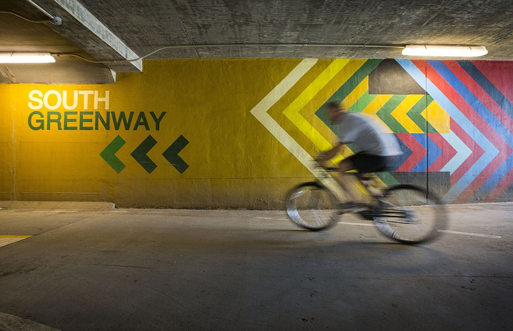 A cyclist rides past a wayfinding mural Saturday, June 13, 2020, inside the Razorback Regional Greenway tunnel at the intersection of Southeast J Street and Southeast 8th Street in Bentonville. The mural was painted in 2018 by Graham Edwards of Bella Vista and features directional guidance for trail users. Go to nwaonline.com/200614Daily/ to see more photos. (NWA Democrat-Gazette/Ben Goff)