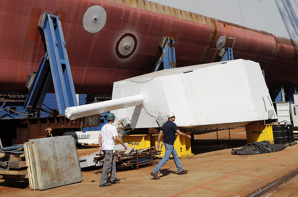 FILE - In this Aug. 29, 2018 file photo, workers walk by the Advanced Gun System, covered in shrink wrap, alongside a Zumwalt-class destroyer being built in the shipyard at Bath Iron Works in Bath, Maine. The largest union at Bath Iron Works begins voting Friday, June 19, 2020 on a contract proposal that was unanimously rejected by its negotiating committee, raising the possibility of the first strike in 20 years. (AP Photo/Robert F. Bukaty, File)