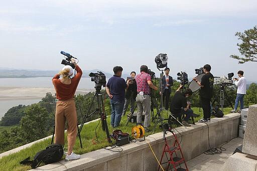 Wartawan mengambil rekaman video dari pos pengamatan unifikasi di Paju, Korea Selatan, dekat perbatasan dengan Korea Utara, Rabu, 17 Juni 2020. Korea Utara mengatakan hari Rabu akan memindahkan pasukan ke lokasi kerja sama antar-Korea yang sekarang ditutup, memasang kembali pos penjagaan dan melanjutkan latihan militer di daerah garis depan, membatalkan kesepakatan pengurangan ketegangan yang dicapai dengan Korea Selatan hanya dua tahun lalu. (Foto AP / Ahn Young-joon)