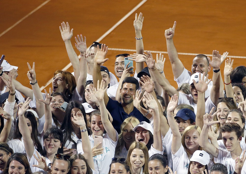 In this photo taken on Sunday, June 14, 2020, Serbia's Novak Djokovic, centre, poses with volunteers and players after the Adria Tour charity tournament in Belgrade, Serbia. Djokovic's charity tennis exhibition series combined with an overall softening of coronavirus restrictions in Serbia has led to a spike in the number the positive cases among professional athletes. Two tennis players ranked among the top 40 in the world and five players at Serbia's biggest soccer club have tested positive for the virus after being involved in sporting events where fans packed into the stands and social distancing was not enforced. (AP Photo/Darko Vojinovic)