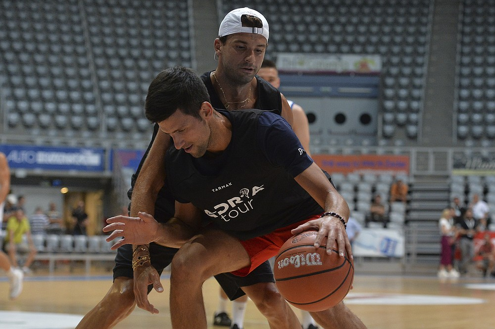 In this photo taken on Thursday June 18, 2020, Bulgarian tennis player Grigor Dimitrov, rear, plays basketball with Serbia's Novak Djokovic in Zadar, Croatia. Dimitrovsays he has tested positive for COVID-19 and his announcement led to the cancellation of an exhibition event in Croatia where Novak Djokovic was scheduled to play on Sunday, June 21. (AP Photo/Zvonko Kucelin)