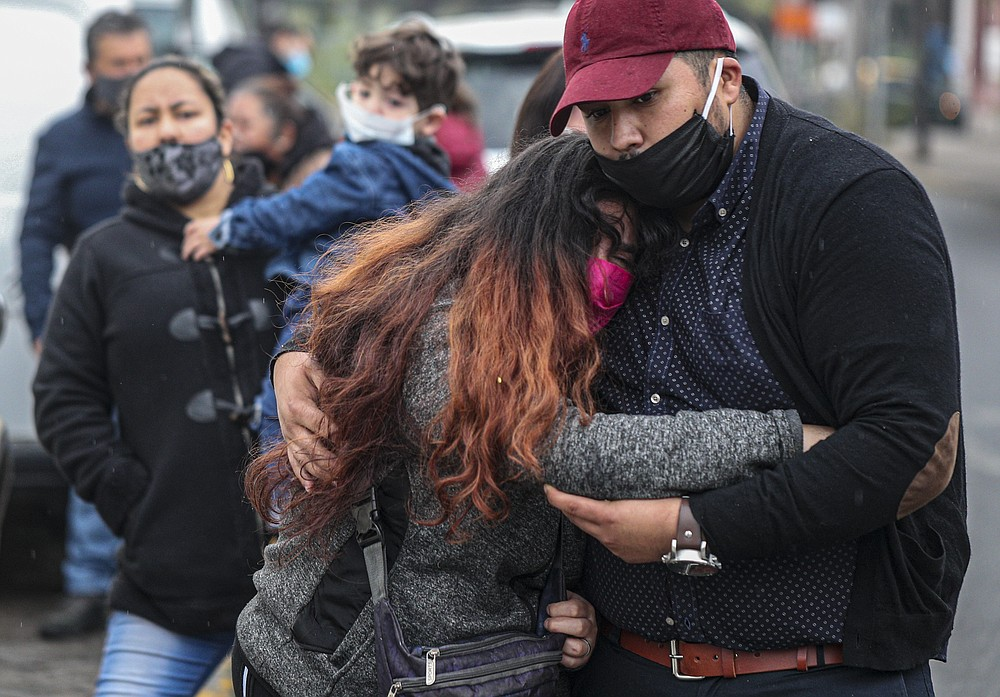 Relatives of Patricio Riveros mourn after his body was brought out in a hearse at the San Jose hospital in Santiago, Chile, Monday, June 22, 2020. Patricio Riveros' son Pedro said that his father died from COVID-19 related complications. (AP Photo/Esteban Felix)