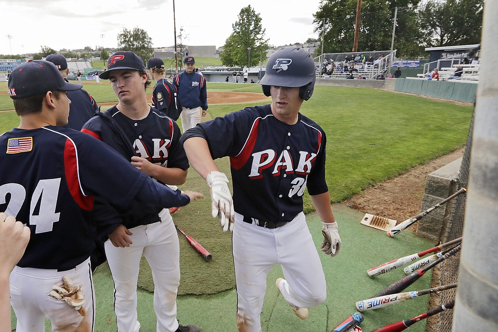 In this photo taken Tuesday, June 16, 2020, Yakima Valley Pepsi Pak baseball players crowd together after they scored a run in their Senior Legion game in Selah, Wash. The team continues to play games despite that they are not approved to do so by the Yakima Health District or allowed under state restrictions so long as Yakima County remains in Phase 1 of the coronavirus reopening. The coronavirus pandemic is hitting Yakima County hard, with cases surging far faster in than in the rest of the state. (AP Photo/Elaine Thompson)