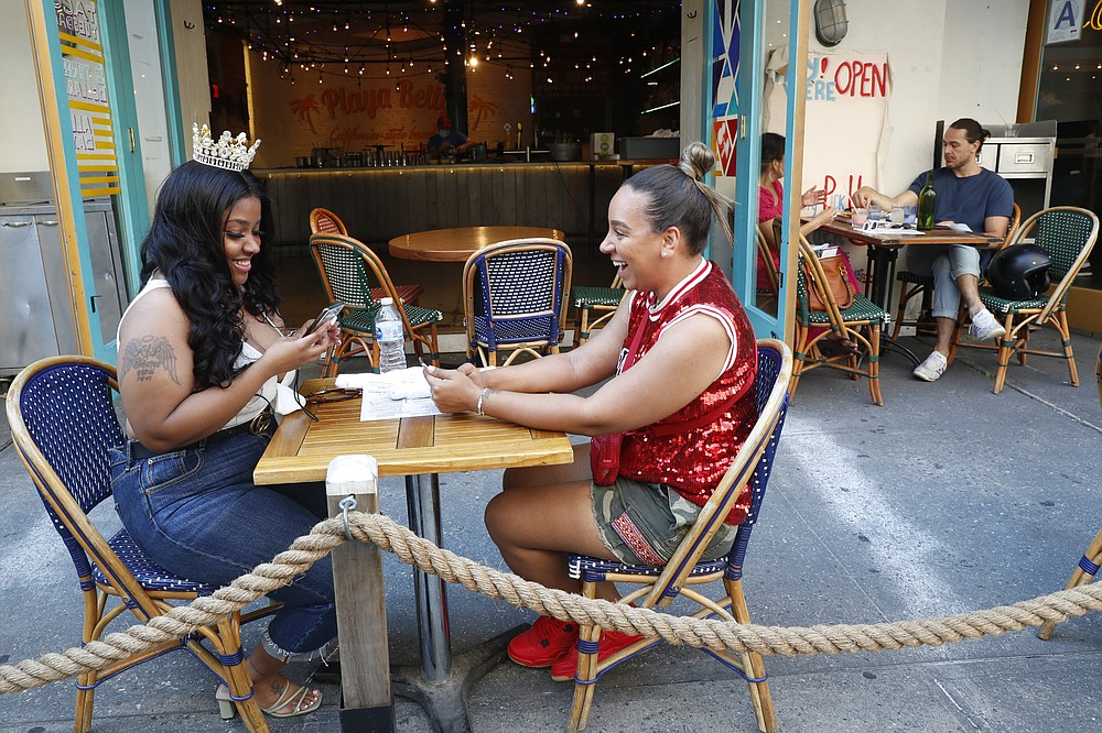 Maya Evans, right, celebrates with friend Tifffany Webster, 30, on Webster's 30th birthday during the first day of the city's phase two reopening from the coronavirus outbreak, Monday, June 22, 2020, on the Upper West Side of Manhattan in New York. Under phase two, the city's restaurants are allowed to serve patrons for outdoor dining with some precautions and restrictions. (AP Photo/Kathy Willens)