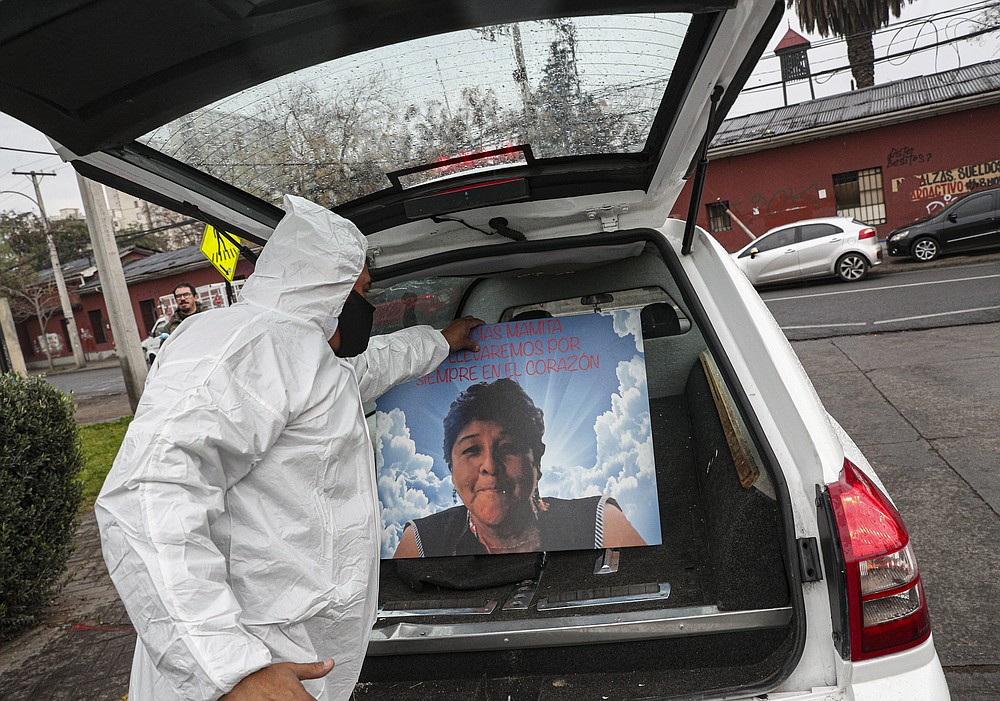 A funeral worker places a picture of Lidia Morales over her coffin in a hearse at the San Jose hospital in Santiago, Chile, Monday, June 22, 2020. Lidia Morales' son Cristian said that his mother died from COVID-19 related complications. (AP Photo/Esteban Felix)