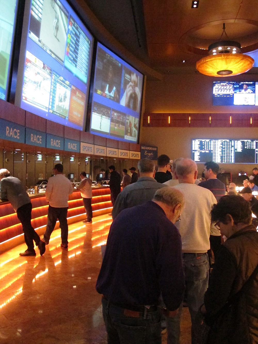 FILE - In this March 21, 2019 file photo, gamblers line up to place bets on the NCAA men's basketball tournament at the Borgata casino in Atlantic City N.J. After being closed since March due to the coronavirus outbreak, the Borgata will reopen to the general public on July 6, 2020 _ four days after much of its competition. Instead, the casino will be doing a test run for an invitation-only audience during those four days. (AP Photo/Wayne Parry, File)
