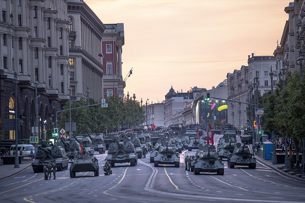FILE - In this file photo taken on Thursday, June 18, 2020, Russian military vehicles prepare to roll along Tverskaya street toward Red Square during a rehearsal for the Victory Day military parade after sunset in Moscow, Russia. A massive military parade that was postponed by the coronavirus will roll through Red Square this week to celebrate the 75th anniversary of the end of World War II in Europe, even though Russia is continuing to register a steady rise in infections. (AP Photo/Alexander Zemlianichenko, File)