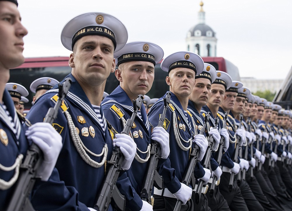 FILE - In this file photo taken on Saturday, June 20, 2020, Russian sailors march toward Red Square to attend a dress rehearsal for the Victory Day military parade in Moscow, Russia. A massive military parade that was postponed by the coronavirus will roll through Red Square this week to celebrate the 75th anniversary of the end of World War II in Europe, even though Russia is continuing to register a steady rise in infections. (AP Photo/Alexander Zemlianichenko, File)