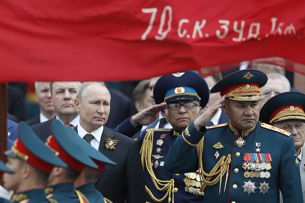 FILE - In this file photo taken on Thursday, May 9, 2019, Russian President Vladimir Putin, left, and Russian Defense Minister Sergei Shoigu, right, attend a wreath-laying ceremony at the Tomb of the Unknown Soldier after the military parade marking 74 years since the victory in WWII in Moscow, Russia. A massive military parade that was postponed by the coronavirus will roll through Red Square this week to celebrate the 75th anniversary of the end of World War II in Europe, even though Russia is continuing to register a steady rise in infections. (AP Photo/Pavel Golovkin, File)