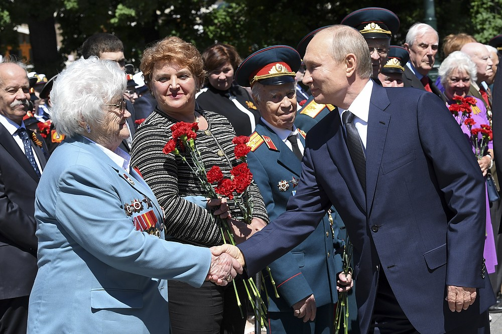 FILE - In this file photo taken on Monday, June 22, 2020, Russian President Vladimir Putin, right, greets a WWII veteran as he arrives to take part in a wreath laying ceremony at the Tomb of Unknown Soldier in Moscow, marking the 79th anniversary of the Nazi invasion of the Soviet Union. A massive military parade that was postponed by the coronavirus will roll through Red Square this week to celebrate the 75th anniversary of the end of World War II in Europe, even though Russia is continuing to register a steady rise in infections. (Alexei Nikolsky, Sputnik, Kremlin Pool Photo via AP, File)