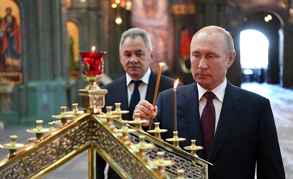 FILE - In this file photo taken on Monday, June 22, 2020, Russian President Vladimir Putin, right, with Russian Defense Minister Sergei Shoigu, lights a candle after a religion service marking the 79th anniversary of the Nazi invasion of the Soviet Union, at the Cathedral of Russian Armed Forces in the Patriot Park outside Moscow, Russia. A massive military parade that was postponed by the coronavirus will roll through Red Square this week to celebrate the 75th anniversary of the end of World War II in Europe, even though Russia is continuing to register a steady rise in infections. (Alexei Nikolsky, Sputnik, Kremlin Pool Photo via AP, File)