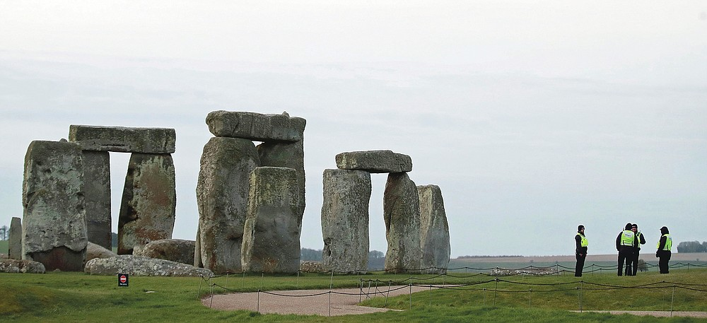 Security staff stand near the ancient Stonehenge site on Salisbury Plain, where the traditional sunrise equinox celebrations inside the stones has been cancelled early Friday March 20, 2020.  The Summer Solstice equinox festival normally held twice yearly is canceled after English Heritage closed the site following government advice on coronavirus. For some people the new COVID-19 coronavirus causes only mild or moderate symptoms, but for some it can cause severe illness. (Adam Davy / PA via AP)