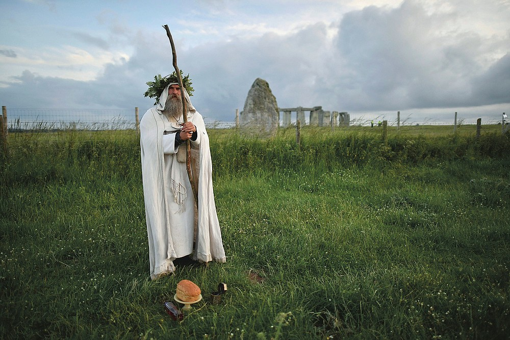 An Archdruid performs a ritual near to the cordoned off Stonehenge as a small group of people gathered to celebrate the Summer Solstice, the longest day of the year, near Salisbury, England, Sunday, June 21, 2020. The coronavirus pandemic has prevented druids, pagans and partygoers from watching the sun rise at Stonehenge to mark the summer solstice. The ancient stone circle usually draws thousands of people to mark the longest day of the year in the northern hemisphere. But Britain has banned mass gatherings as part of measures to contain the spread of COVID-19. English Heritage, the body that oversees Stonehenge, livestreamed the sunrise instead.  (Ben Birchall/PA via AP)