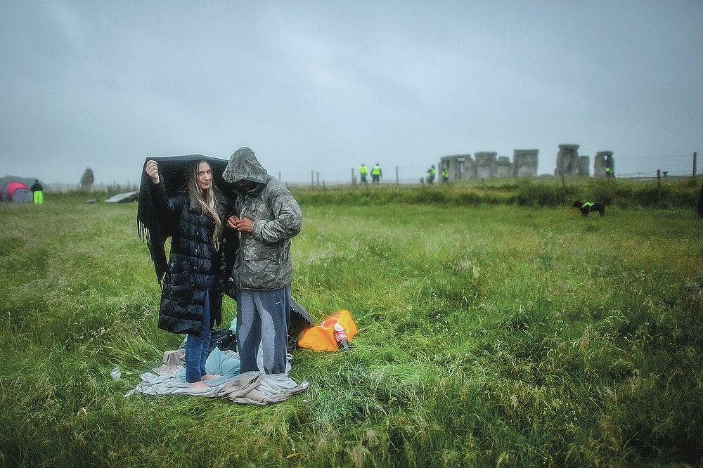 People shield from the rain next to the closed Stonehenge as people gather to celebrate the Summer Solstice, the longest day of the year, near Salisbury, England, Sunday June 21, 2020. (Ben Birchall/PA via AP)