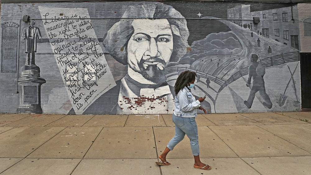 A woman, wearing a protective mask due to the COVID-19 virus outbreak, walks past a mural in tribute to Frederick Douglass on Wednesday, June 24, 2020, in the South End neighborhood of Boston. (AP Photo/Charles Krupa)