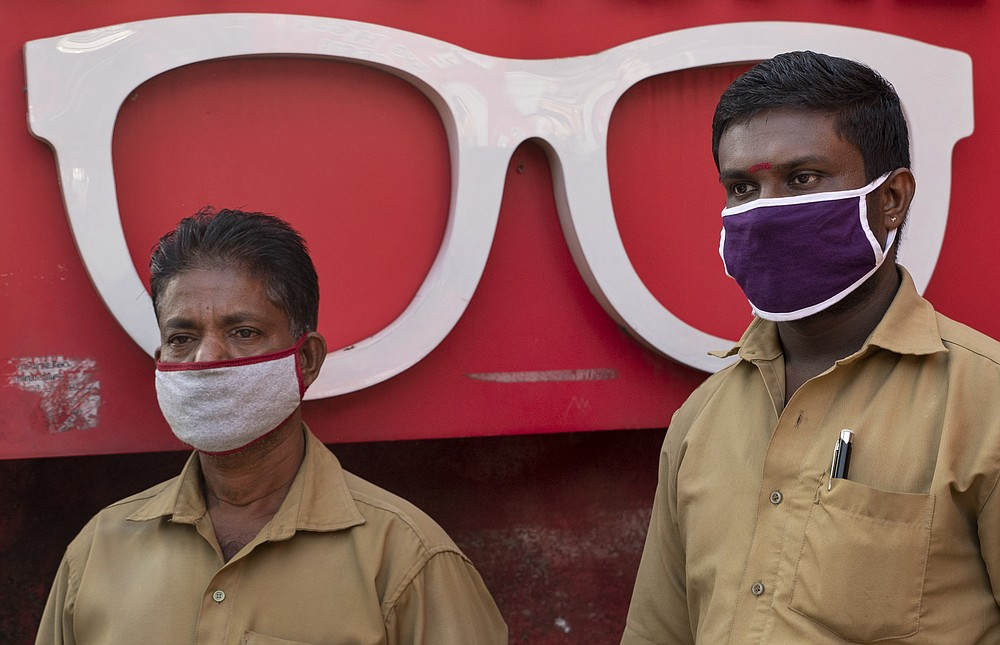 Auto rickshaw drivers wearing masks as a precaution against COVID-19 await customers near an optical shop in Kochi, Kerala state, India, Wednesday, June 24, 2020. India is the fourth hardest-hit country by the coronavirus in the world after the U.S., Russia and Brazil. (AP Photo/R S Iyer)