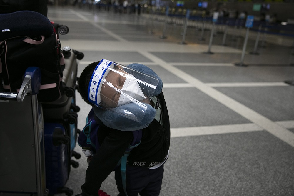 A young boy, who is traveling to China, stretches in the ticketing area at the Los Angeles International Airport, Wednesday, June 24, 2020, in Los Angeles. The U.S. recorded a one-day total of 34,700 new COVID-19 cases, the highest in two months, according to the count kept by Johns Hopkins University. (AP Photo/Jae C. Hong)